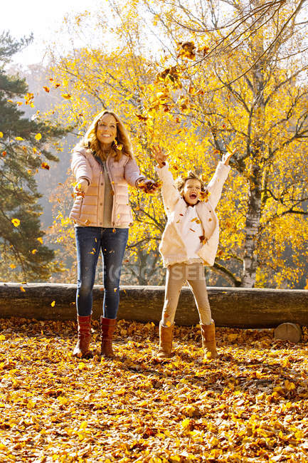 Mother and her little daughter throwing autumn leaves into the air — Stock Photo
