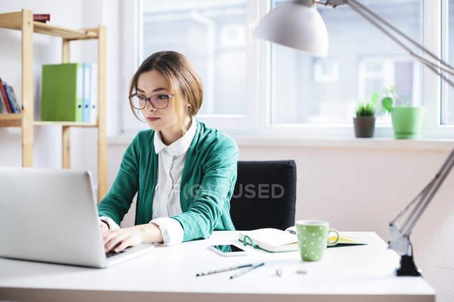 Giovane donna d'affari alla scrivania in ufficio — Foto stock