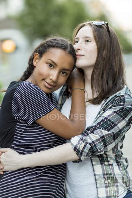 Две девочки-подростки обнимаются на улице — стоковое фото