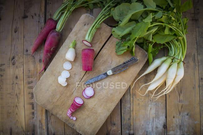 Rodajas de rábano rojo orgánico y rábano blanco sobre tablero de madera - foto de stock