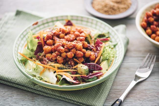 Gemischte rohe Salat mit geräuchertem Paprika, Honig, Sojasauce und Kichererbsen auf Platte — Stockfoto
