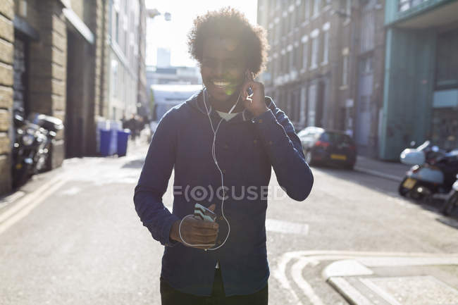 Young man listening to music from cell phone on urban street — Stock Photo