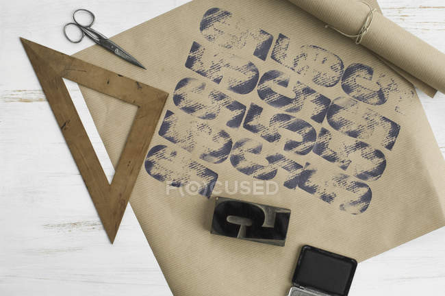 Printed packing paper with triangle, stamp and ink pad — Stock Photo