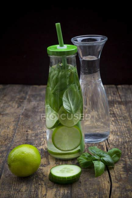 Стеклянная бутылка воды с лаймом, огурцом и базиликом — стоковое фото