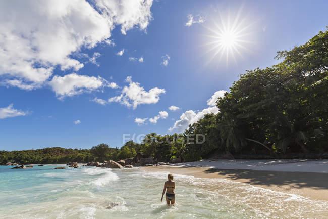 Seychelles, Praslin, Anse Lazio, praia, turista feminina na água — Fotografia de Stock