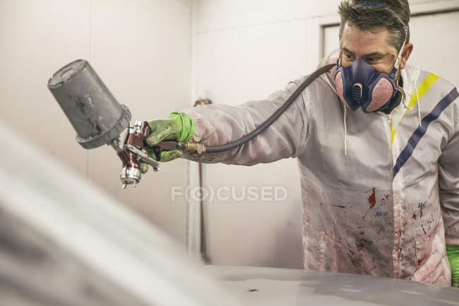 Closeup of middle aged man in mask painting car — Stock Photo