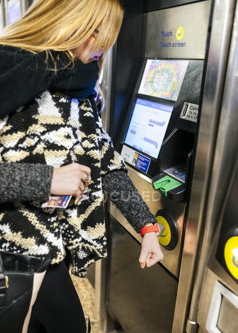Young woman paying with her smartwatch on the subway — Stock Photo