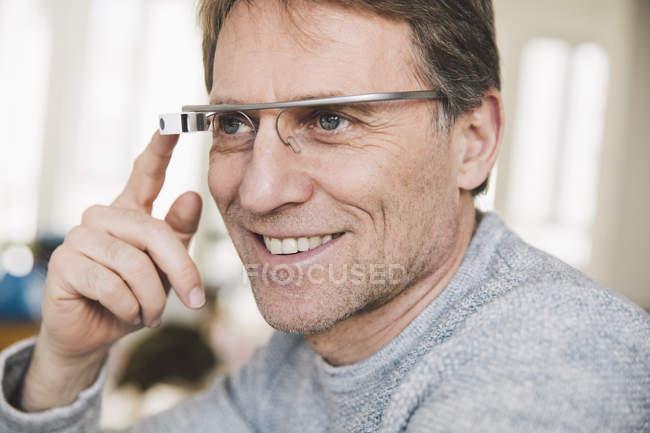 Homme souriant portant un écran optique monté sur la tête — Photo de stock