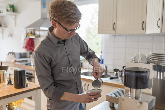 Man pouring milk froth in coffee cup — Stock Photo