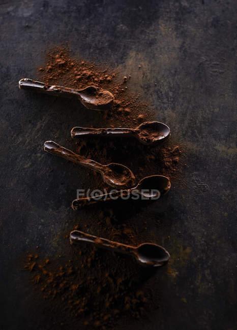 Fünf Löffel Schokolade mit Kakao bestreut — Stockfoto