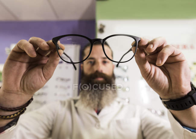 Optometrist looking at glasses — Stock Photo