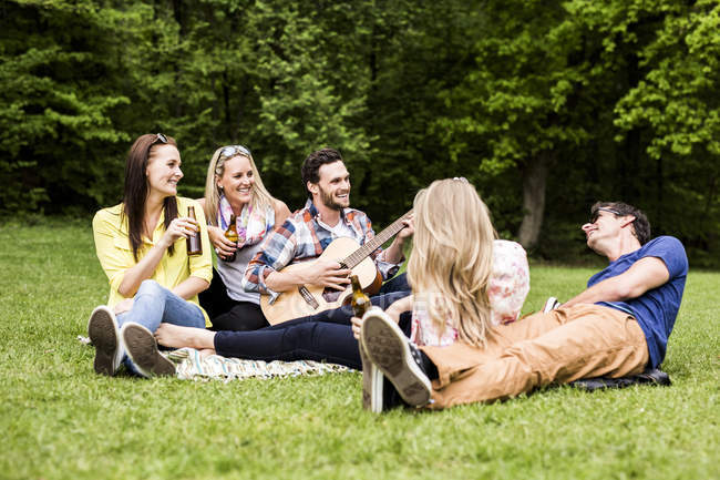 Happy friends with guitar and beer bottles relaxing in park — Stock Photo
