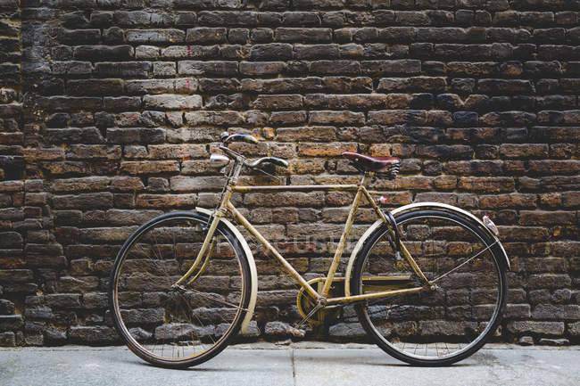Vintage bicycle leaning against a brick wall — Stock Photo