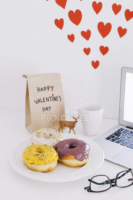 Still life with laptop, donuts, Valentines day present and hearts on wall — Stock Photo