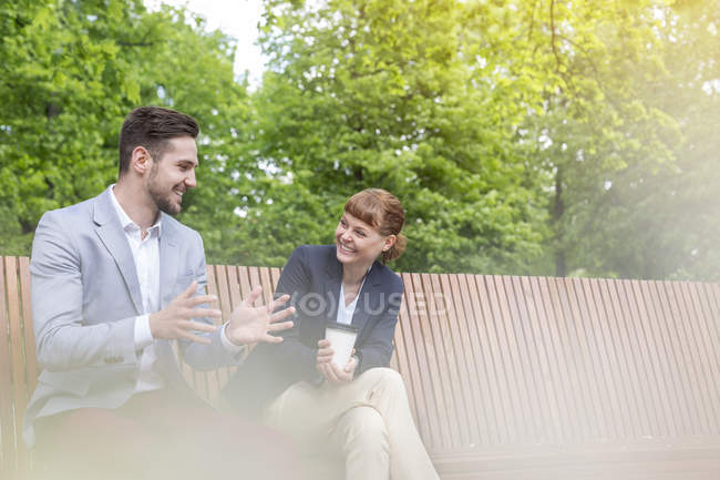 Amazing Two Young Business People Sitting On Wooden Bench And Bralicious Painted Fabric Chair Ideas Braliciousco