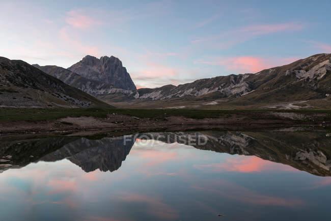 Italy, Abruzzo, Gran Sasso e Monti della Laga National Park, plateau Campo Imperatore, Corno Grande peak reflected in lake Petranzoni at sunset — Stock Photo