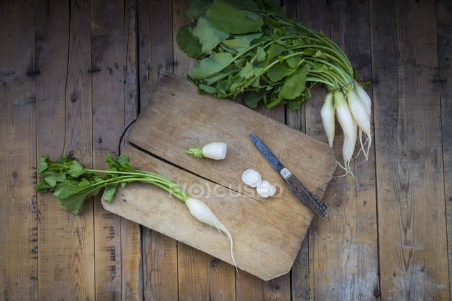 Sliced and whole white radish on wooden board — Stock Photo