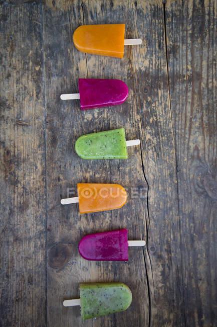 Row of fruit smoothie ice lollies on dark wood — Stock Photo