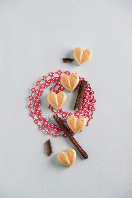 Heart shape bath pralines with cinnamon sticks — Stock Photo