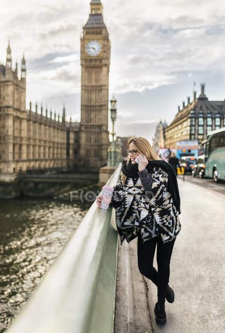 Reino Unido, Londres, jovem mulher falando por telefone em Westminster Bridge — Fotografia de Stock