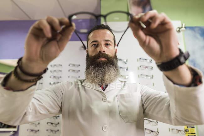 Optometrist checking glasses in store — Stock Photo