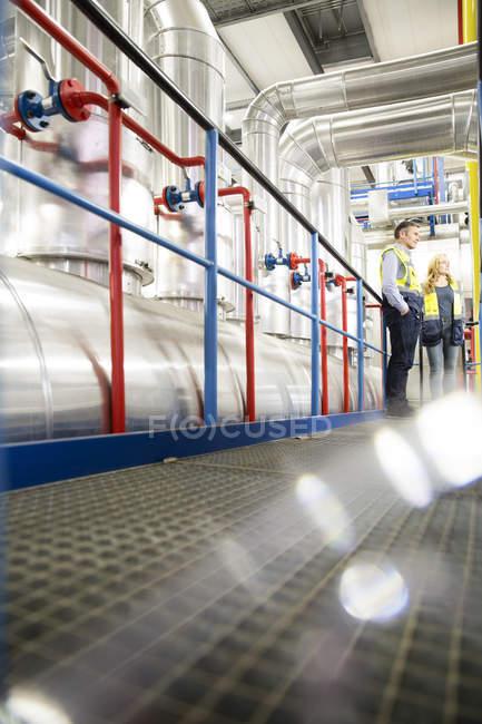 Kollegen mit Warnwesten stehen in Industrieanlage — Stockfoto