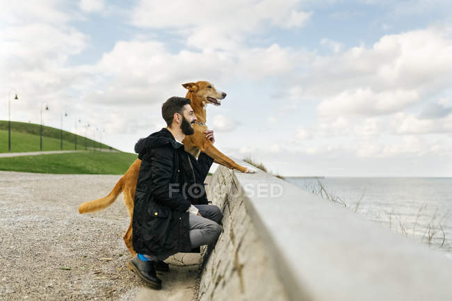 Man and his dog looking at the sea — Stock Photo