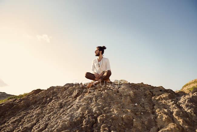 Человек, сидя на холме — стоковое фото