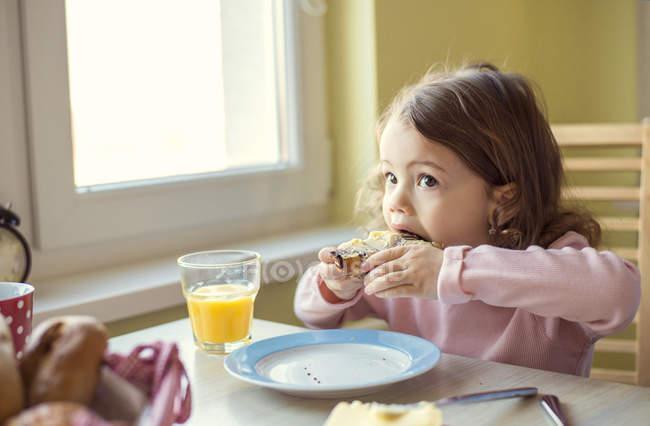 Маленькая девочка ест круассан на стол завтрак — стоковое фото