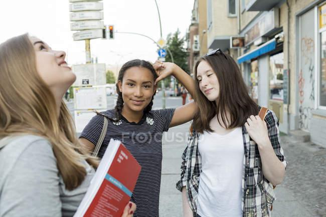 Tres adolescentes en su camino a la escuela - foto de stock