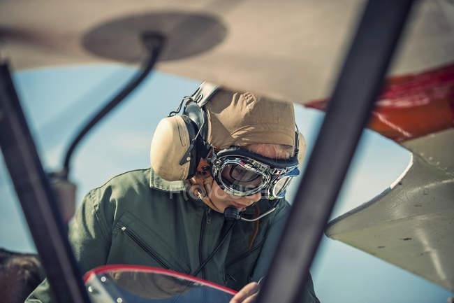 Garçon assis en biplan portant une vieille tenue de pilote — Photo de stock