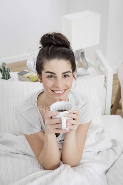 Ritratto di giovane donna sorridente con tazza di caffè a letto — Foto stock