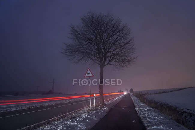 Dribing cars on road, fog in the evening, long exposure, Lower Saxony, Germany — Stock Photo