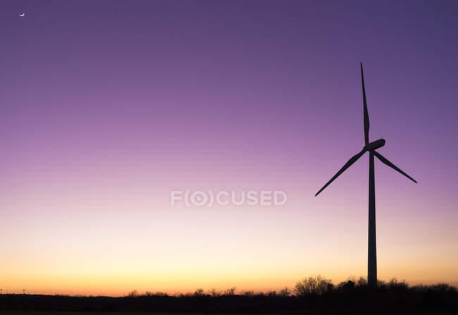 Roue de vent dans une prairie au coucher du soleil — Photo de stock