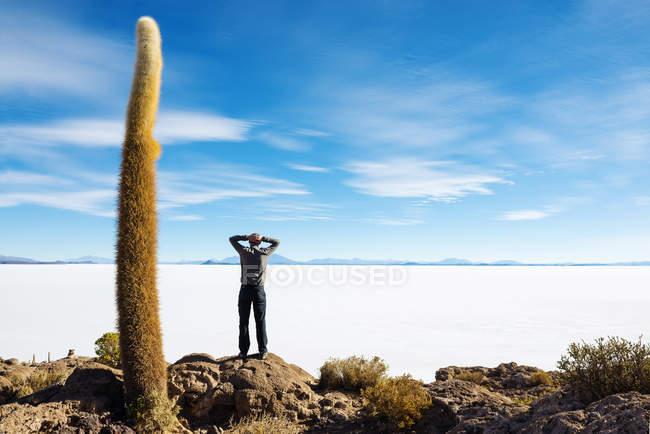 Atacama, Altiplano, Salar de Uyuni, Bolivien, Mann stehend und mit Blick auf Salzsee — Stockfoto