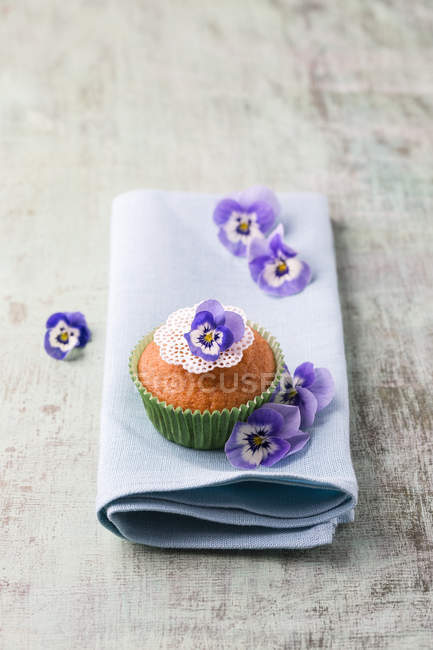 Muffin decorated with edible flowers on napkin — Stock Photo