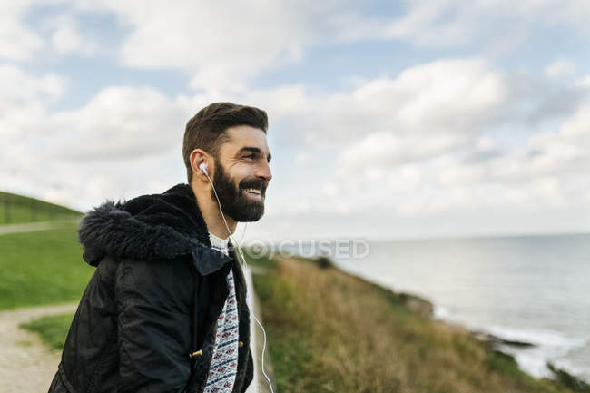 Portrait of bearded man listening music with earphones — Stock Photo
