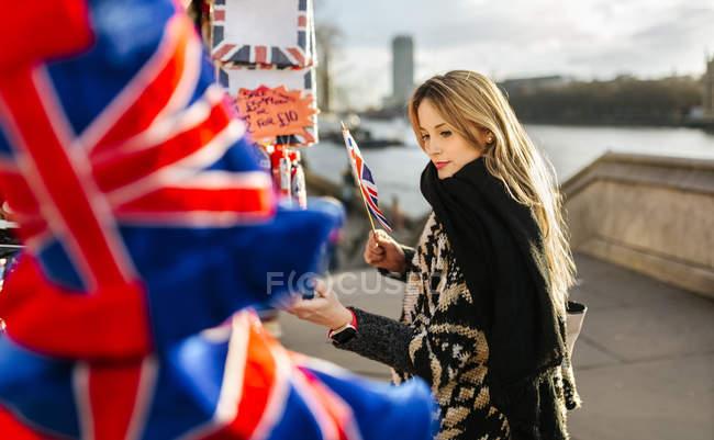 Великобританія, Лондон, молода жінка, дивлячись на зрив сувенірні — стокове фото