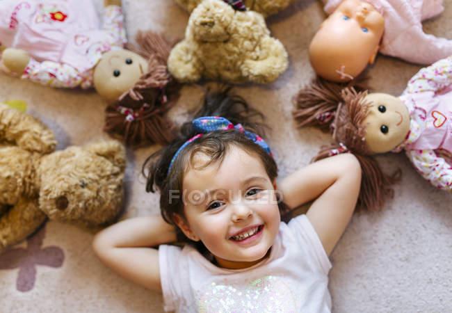 Сміючись дівчинка лежав на підлозі з полки і ляльки — стокове фото