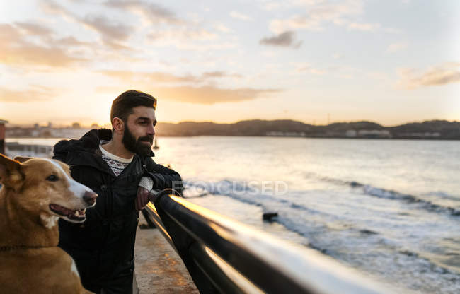Smiling man and his dog at sunset — Stock Photo