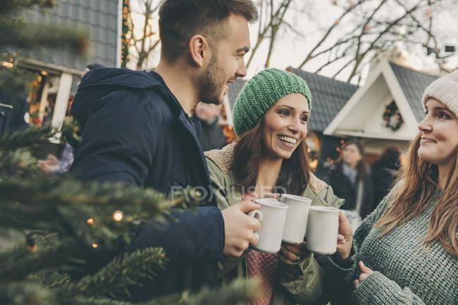 Трьох друзів, що мають гарячий пунш на Різдвяний ярмарок — стокове фото