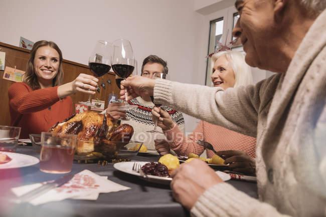 Сім'ї цокаючись під час Різдвяна вечеря — стокове фото