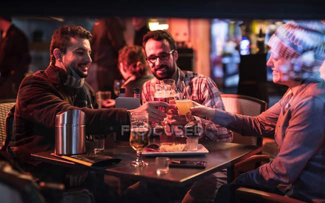 Três amigos tilintar de copos de cerveja no pub à noite — Fotografia de Stock