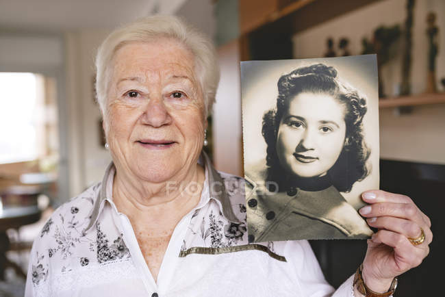 Portrait of senior woman showing an old picture of herself — Stock Photo