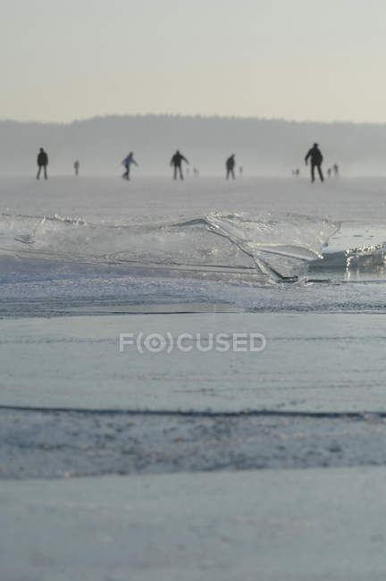 Германия, люди на коньках на замерзшем озере с тонкой ледникового — стоковое фото