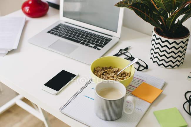 Робоче місце на домашньому офісі і ноутбук на стіл з харчування й телефонні — стокове фото