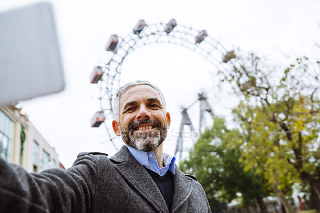 Portrait of smiling businessman taking a selfie at Prater — Stock Photo