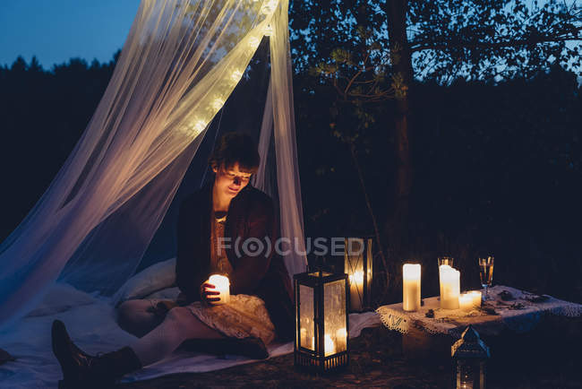 Happy woman in a romantic camp in autumnal nature by candle lights — Stock Photo