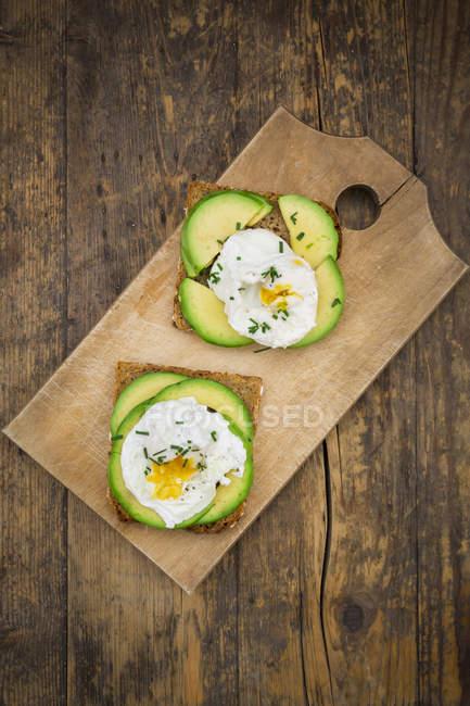 Скибочки хліб з непросіяного борошна з скибочками авокадо і вареними яйцями на дерев'яну шахівницю — стокове фото