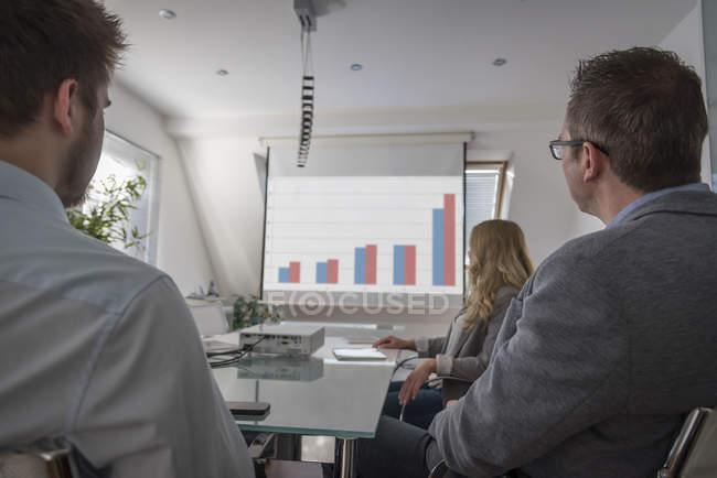 Colleghi che partecipano a una presentazione con grafici a barre sullo schermo di proiezione — Foto stock